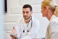 Arzt mit Patrientin und Tablet PC