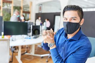 Junger Business Mann im Büro mit Mund-Nasen-Schutz