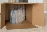 Small product wrapped in plastic wrap inside very large cardboard shipping box