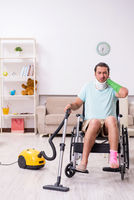 Young man in wheel-chair cleaning the house