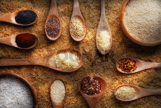 Flat lay still life with brown rice, bowls and spoons with various rices, grains and spices.