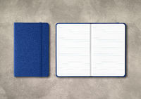 Marine blue closed and open lined notebooks on concrete background
