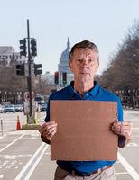 Senior man holding a blank cardboard sign in Pennsylvania Avenue, DC