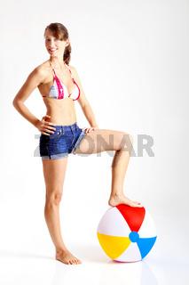 Beautiful young woman posing in bikini with a beach ball