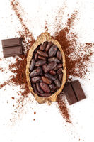 Cocoa beans, powder and chocolate on white background from above.