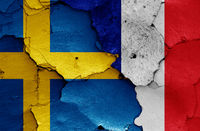 flags of Sweden and France painted on cracked wall