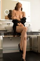 Topless slim woman undress black shirt in bathroom