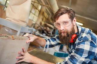 Hipster Tischler mit Bart in Ausbildung beim Hobeln