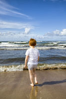 a small child walking on the shore