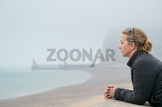 Woman looking out over a foggy sea