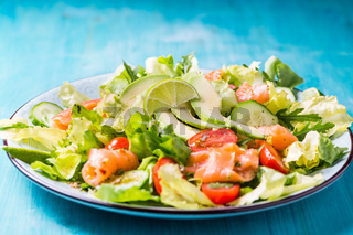 Healthy salad with smoked samlmon and avocado on cyan vackground