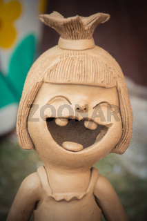 Happy Ceramic dolls for garden decoration. Cute ceramic clay pottery of girl show her up-swept bun and broken tooth that happy laughing until her eyes closed. Happy dolls for garden decoration.