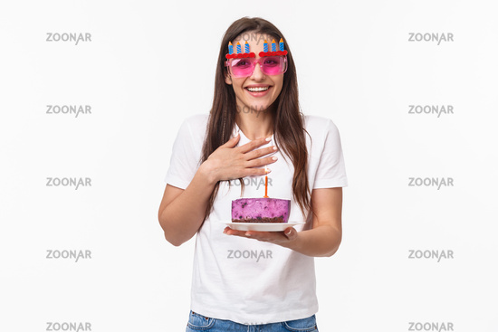 Entertainment, fun and holidays concept. Thankful surprised cute girl celebrating birthday, receive piece cake with lit candle, making b-day wish, wear funny glasses, smiling and laughing happy
