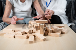 Dementia therapy in playful way, training fingers and fine motor skills, build wooden blocks into tower, playing Jenga. Senior woman 90 years old and doctor playing educational game in nursing home