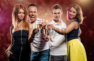 Cheerful group of young people with glasses of sparkling champagne over abstract background