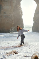 Cheery lively playful young woman enjoy surf of Atlantic Ocean foamy wavy waters laughing spend vacation on the beach in Lagos, Algarve, Portugal. Vertical image concept of tourism free time holidays
