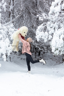 Happy go lucky woman frolicking in snow holding large soft toy