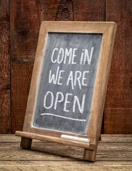 Come in, we are open invitation, blackboard sign.
