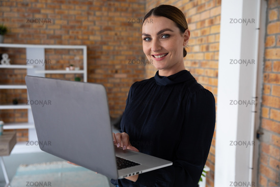 Portrait of woman using laptop while standing
