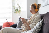 Social distancing. Stay at home. Woman in bathrobe being comfortable at her home sofa, using social media apps on phone for video chatting and stying connected with her loved ones.