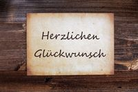 Old Paper, Glueckwunsch Means Congratulations, Wooden Background