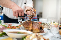 Man divides with scissors freshly baked duck into portions, process close up. Events take place at home during a family meeting to celebrate the solemn event. Foods and dishes on the table
