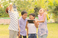 Group of Children laughing by seeing media on mobile - kids having fun by by looking on Smartphone - concept of teens addicted to cellphones and technology.