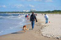 Urlauber beim Spaziergang am Strand von Swinemünde