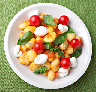 Homemade gnocchi with tomato sauce basil and mozzarella.