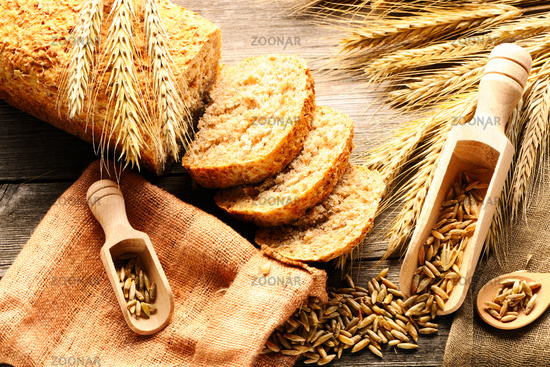 Rye spikelets and bread still life on wooden background