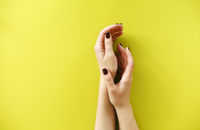 Woman with manicure placing hands over yellow background