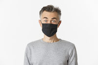 Concept of covid-19, social distancing and quarantine. Close-up of surprised middle-aged man in black medical mask, hear fantastic offer, look amazed at camera, standing over white background