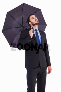 Businesswoman in suit holding umbrella while looking up