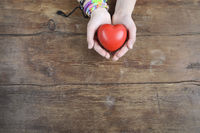 heart in hands on wood