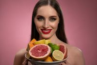 Fruit salad for cosmetic mask for girl face with natural make up and bare shoulders. Healthy pure skin model isolated on black background. Natural make up, spa and beautiful concept