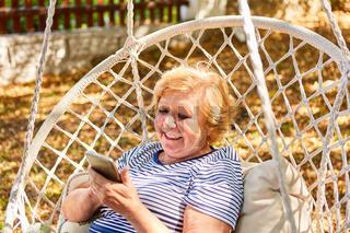 Seniorin mit Smartphone schreibt eine SMS