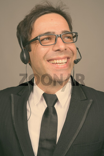 Handsome Persian businessman working as call center representative against gray background