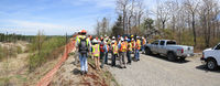 SUDBURY, ONTARIO, CANADA - MAY 21 2009: Group of workers and geologists in hardhats and high-visibility vests standing on road.