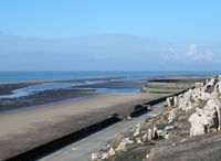 the cliffs area on the south promenade in Blackpool with the beach at low tide on a bright sunlit day