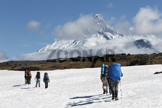 Hiking on Kamchatka Peninsula: hiker goes in mountain on background of Klyuchevskaya group of volcan