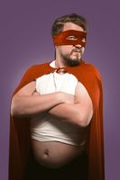 Super hero man with crossed arms and opened tummy looking at camera. Serious man in cape and superhero costume isolated on grape purple background. Power concept