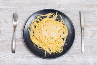 pasta with butter and cheese and fork with knife