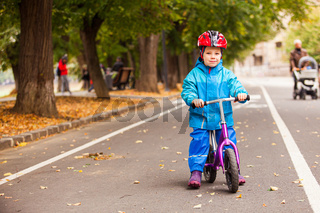 Toddler boy in blue autumn clothes on his bike