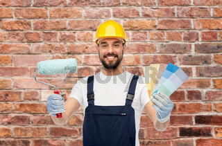 male builder with paint roller and color palettes