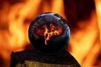 Lagerfeuer in einer mit Steinen umfassen Feuerstelle spiegelt sich in ein Glaskugel
