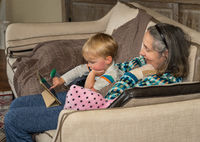 Young toddler playing on digital tablet while sitting on sofa with grandma