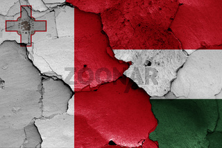 flags of Malta and Hungary painted on cracked wall