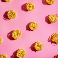 Pasta art with tagliatelle on pink background