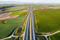 Aerial view of a highway with cars and trucks, in a beautiful countryside scenery.