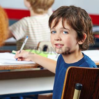 Lächelndes Kind sitzt am Tisch in Schule
